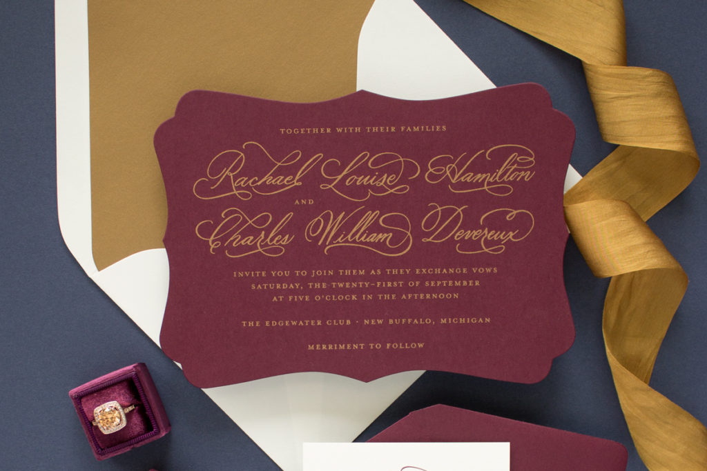 gold and burgundy wedding invitation with calligraphy