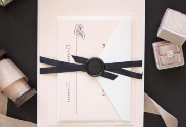 These classic letterpress invitations for a black tie wedding featured black text on blush pink paper, tied up with a silk ribbon and topped with a monogram wax seal.