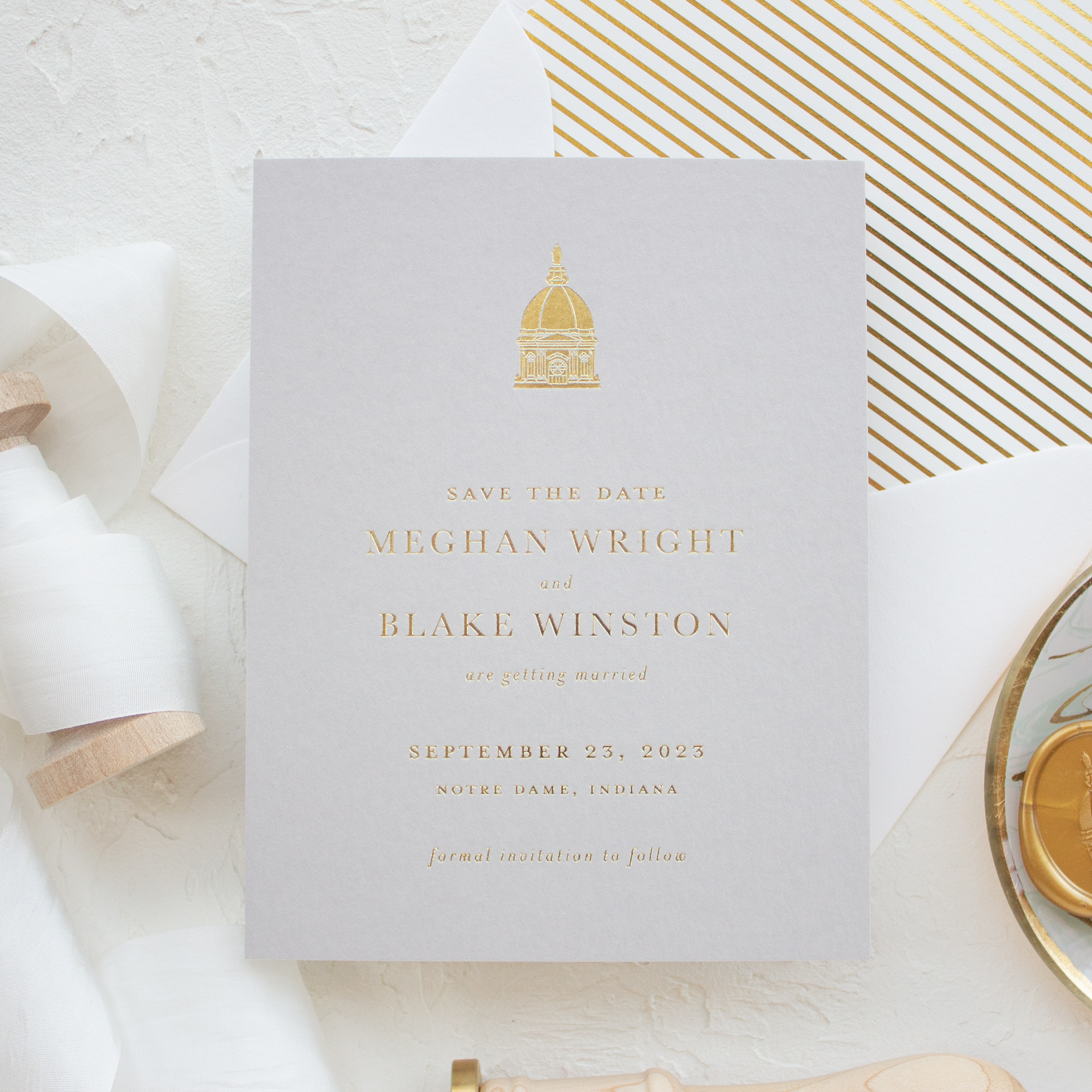 save the date card in gold foil with venue illustration of Notre Dame
